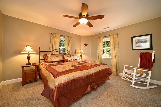 queen sized bed and chair in bedroom at astonishing views a 2 bedroom cabin rental located in gatlinburg