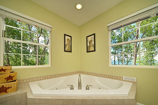 jacuzzi tub in bathroom corner with natural light through windows on each side at astonishing views a 2 bedroom cabin rental located in gatlinburg