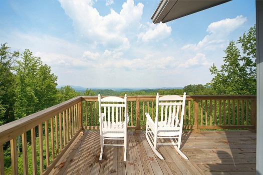 White rocking chairs on the deck at Astonishing Views, a 2-bedroom cabin rental located in Gatlinburg