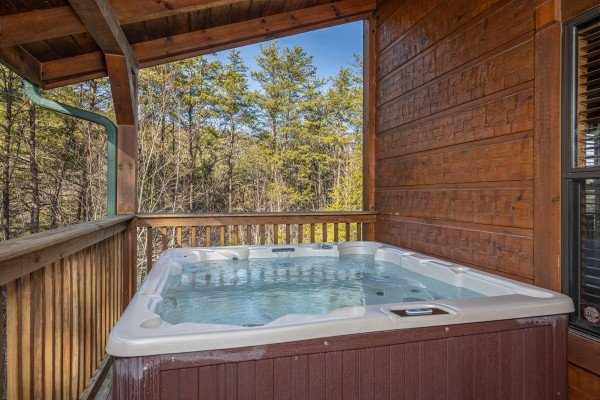 Hot tub on a covered deck at King of the Mountain, a 3 bedroom cabin rental located in Pigeon Forge