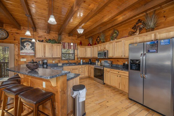 Island breakfast bar in a kitchen with stainless appliances at King of the Mountain, a 3 bedroom cabin rental located in Pigeon Forge