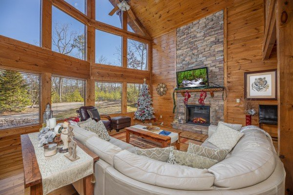 Large windows, fireplace, and TV in the living room at King of the Mountain, a 3 bedroom cabin rental located in Pigeon Forge