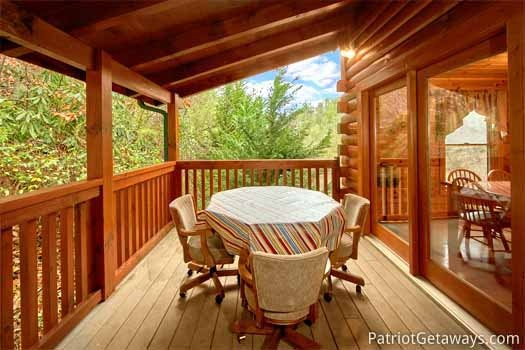 four cushioned chairs around table at black bear lodge a 5 bedroom cabin rental located in pigeon forge