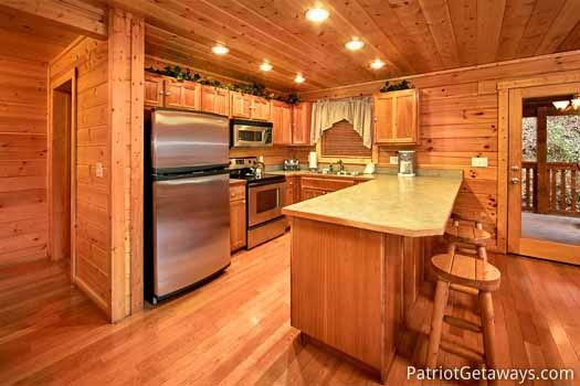 kitchen with bar and stools at black bear lodge a 5 bedroom cabin rental located in pigeon forge