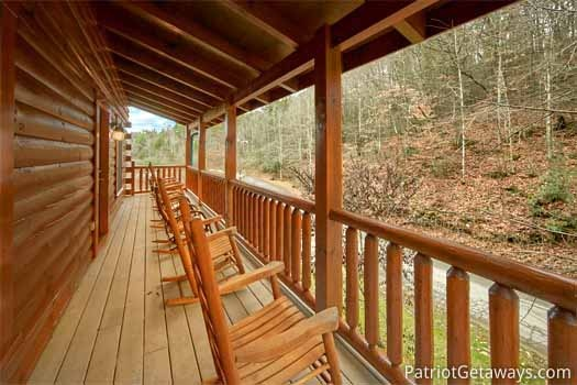 rocking chairs lined up across the deck at black bear lodge a 5 bedroom cabin rental located in pigeon forge