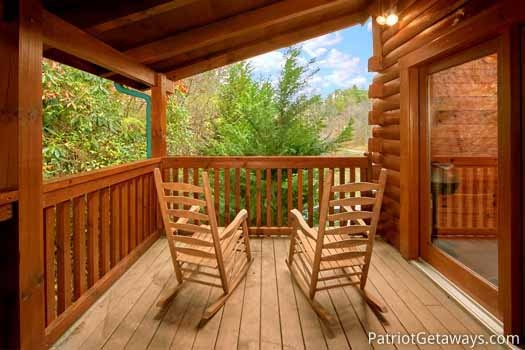 two rocking chairs on the deck at black bear lodge a 5 bedroom cabin rental located in pigeon forge