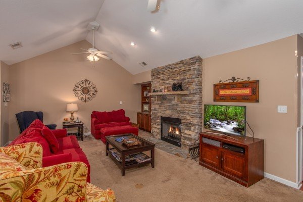 Stacked stone fireplace in a vaulted living room at Autumn Blaze, a 2-bedroom cabin rental located in Pigeon Forge