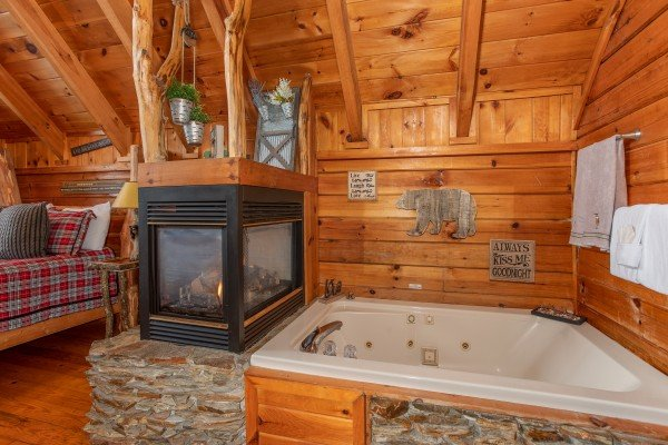 Fireplace and jacuzzi tub in the bedroom at Woodland Chalet, a 1 bedroom cabin rental located in Pigeon Forge