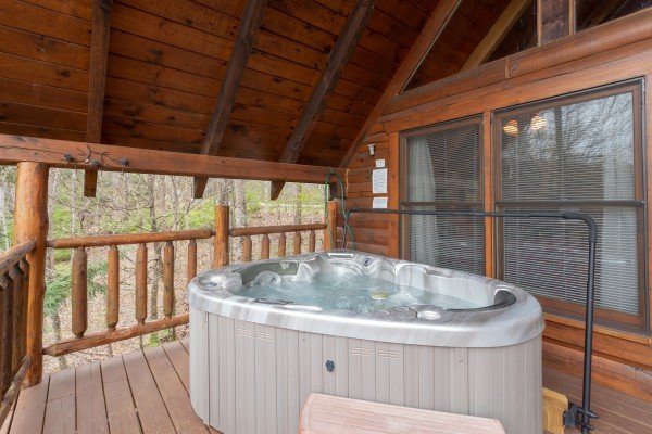 Hot tub on a covered deck at Woodland Chalet, a 1 bedroom cabin rental located in Pigeon Forge
