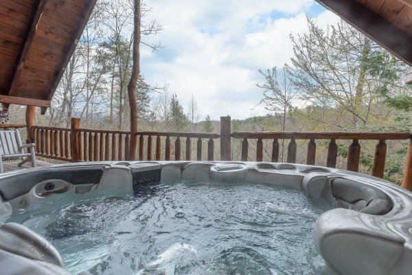 Hot tub on a covered deck with mountain views at Woodland Chalet, a 1 bedroom cabin rental located in Pigeon Forge