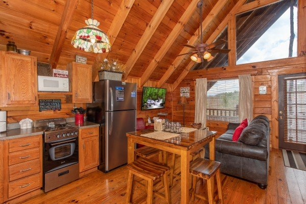 Kitchen with stainless appliances and dining space at Woodland Chalet, a 1 bedroom cabin rental located in Pigeon Forge