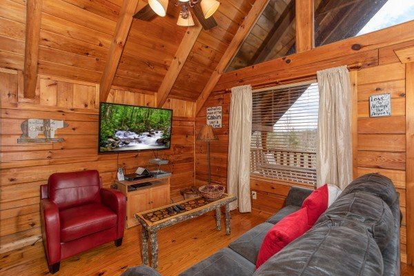 Living room with TV and table at Woodland Chalet, a 1 bedroom cabin rental located in Pigeon Forge