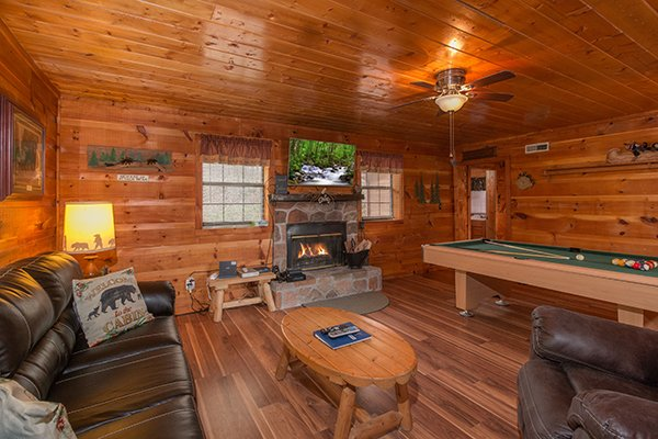 Living room with a fireplace, television, and pool table at Beary Good Time, a 1-bedroom cabin rental located in Pigeon Forge