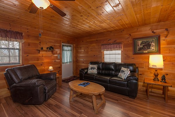 Living room with a leather sofa and oversized leather recliner at Beary Good Time, a 1-bedroom cabin rental located in Pigeon Forge