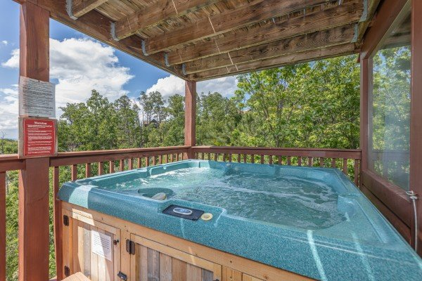 Hot tub on a covered deck at Smoky Mountain High, a 1 bedroom cabin rental located in Pigeon Forge