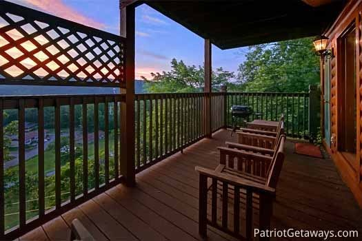 deck with seating and grill at night lights lodge a 7 bedroom cabin rental located in gatlinburg