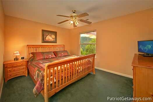 first floor king sized bedroom at night lights lodge a 7 bedroom cabin rental located in gatlinburg