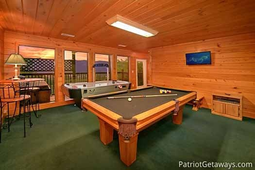 game room with pool table and air hockey table at night lights lodge a 7 bedroom cabin rental located in gatlinburg