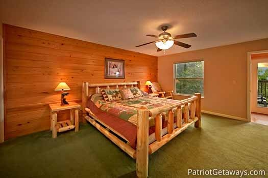 main level king bedroom at night lights lodge a 7 bedroom cabin rental located in gatlinburg
