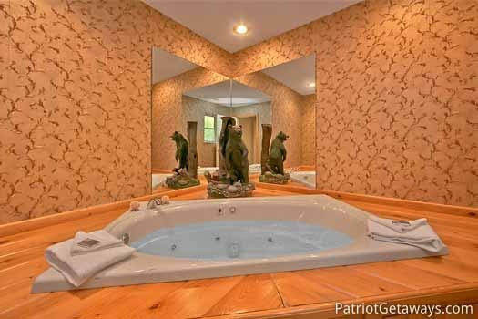 third floor bathroom with jacuzzi tub at night lights lodge a 7 bedroom cabin rental located in gatlinburg