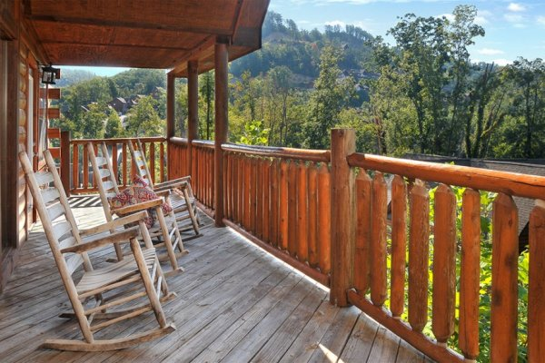 Covered deck with rocking chairs overlooking the woods at Kick Back & Relax! A 4 bedroom cabin rental located in Pigeon Forge