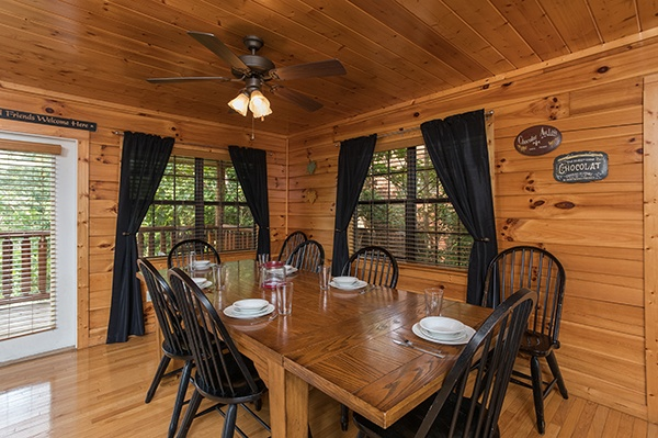Dining table with seating for six and two extra chairs at Kick Back & Relax! A 4 bedroom cabin rental located in Pigeon Forge
