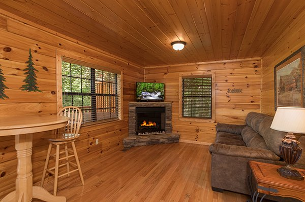 Sofa, TV, fireplace, and high top dining table in the downstairs living room at Kick Back & Relax! A 4 bedroom cabin rental located in Pigeon Forge