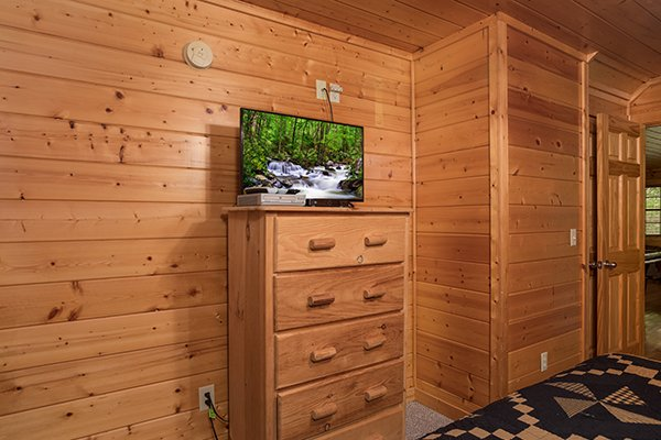 Bedroom with a TV and dresser at Kick Back & Relax! A 4 bedroom cabin rental located in Pigeon Forge