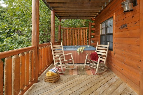 Hot tub and rocking chairs on a covered deck at Kick Back & Relax! A 4 bedroom cabin rental located in Pigeon Forge