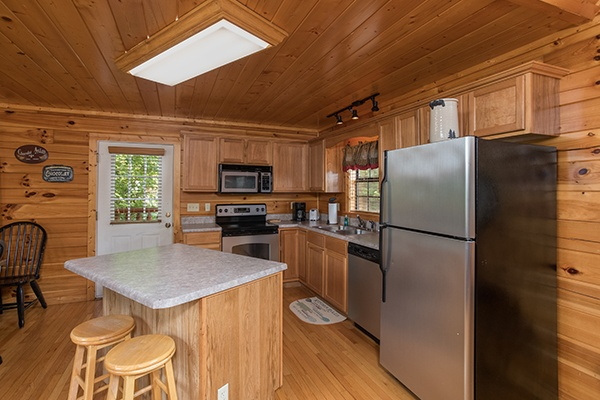 Kitchen with stainless steel appliances and an island with counter seating at Kick Back & Relax! A 4 bedroom cabin rental located in Pigeon Forge