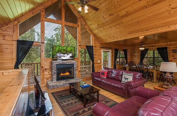 Living room with high ceiling and floor to ceiling windows at Kick Back & Relax! A 4 bedroom cabin rental located in Pigeon Forge