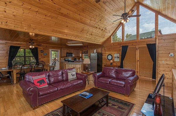 Open concept living, dining, and kitchen space with high windows and natural light at Kick Back & Relax! A 4 bedroom cabin rental located in Pigeon Forge