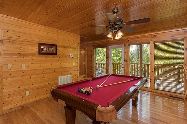 Red felt pool table and deck access in the game room at Kick Back & Relax! A 4 bedroom cabin rental located in Pigeon Forge