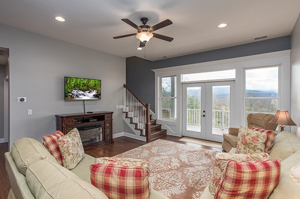 First floor living room with TV and deck access at Summit Glory, a 5 bedroom cabin rental located in Pigeon Forge