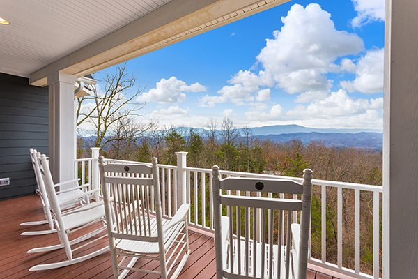 Rocking chairs on a covered deck facing Smoky Mountain views at Summit Glory, a 5 bedroom cabin rental located in Pigeon Forge