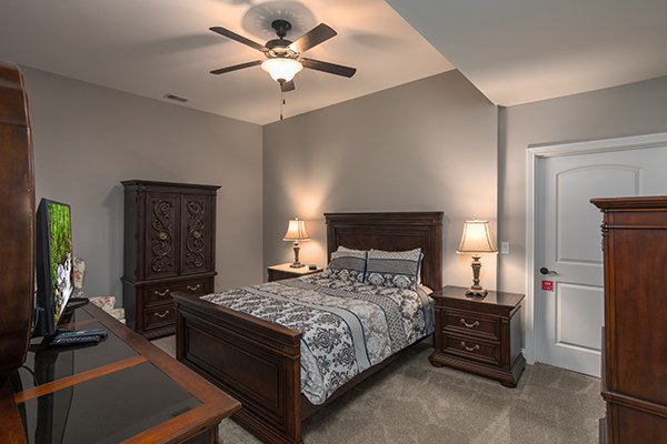 Queen bedroom with armoire, dresser, and TV at Summit Glory, a 5 bedroom cabin rental located in Pigeon Forge