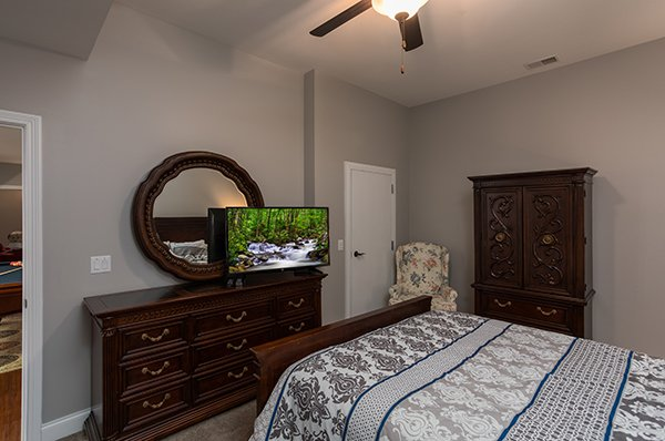 Dresser with mirror and TV in a bedroom at Summit Glory, a 5 bedroom cabin rental located in Pigeon Forge