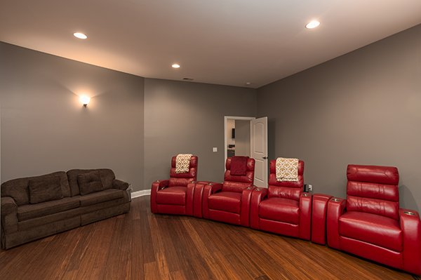 Four large recliners and a sofa in the theater room at Summit Glory, a 5 bedroom cabin rental located in Pigeon Forge