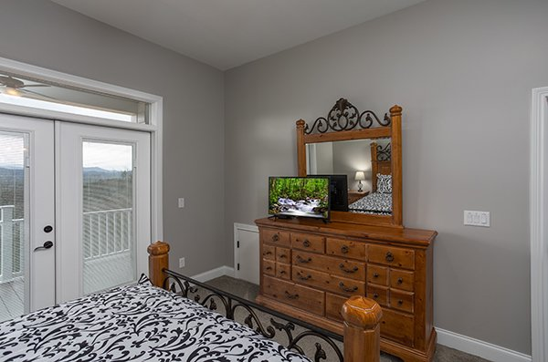 Bedroom with dresser, TV, and deck access at Summit Glory, a 5 bedroom cabin rental located in Pigeon Forge
