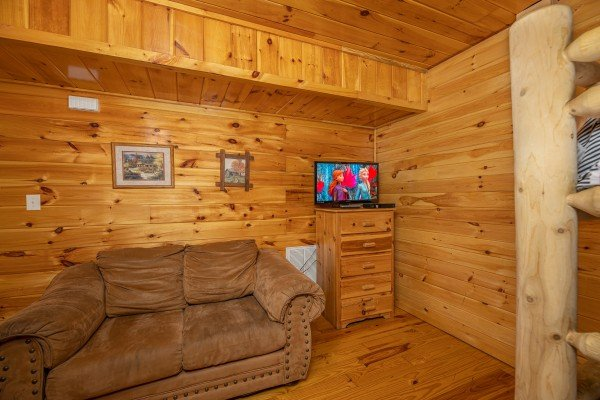 Sofa & Dresser with TV at Hickernut Lodge, a 5-bedroom cabin rental located in Pigeon Forge