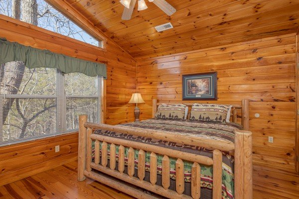 Loft bedroom with a king log bed, night stand, and lamp at Hickernut Lodge, a 5-bedroom cabin rental located in Pigeon Forge