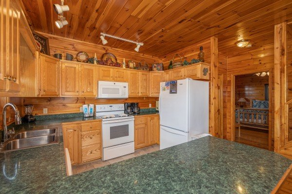 Kitchen with white appliances at Hickernut Lodge, a 5-bedroom cabin rental located in Pigeon Forge