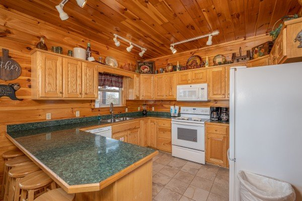 Breakfast bar and kitchen with white appliances at Hickernut Lodge, a 5-bedroom cabin rental located in Pigeon Forge