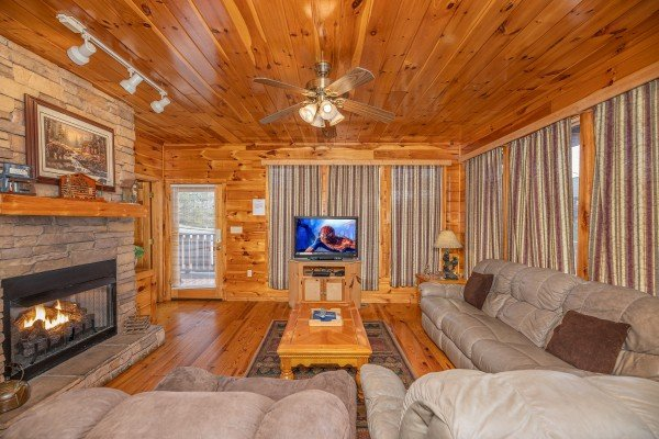 Main living room with TV, fireplace, and seating at Hickernut Lodge, a 5-bedroom cabin rental located in Pigeon Forge