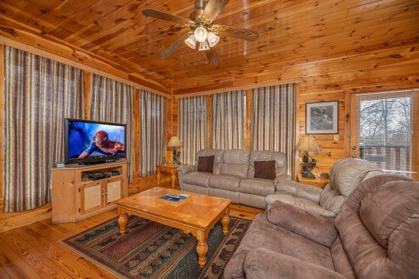 TV and sofas in the living room at Hickernut Lodge, a 5-bedroom cabin rental located in Pigeon Forge