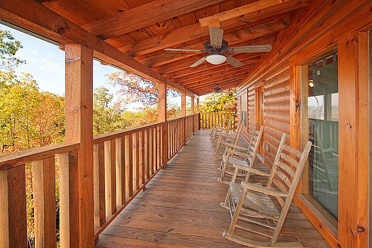 Rockers on a covered deck at Hickernut Lodge, a 5-bedroom cabin rental located in Pigeon Forge