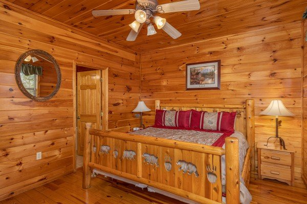 Bedroom with king bed, two night stands, and two lamps at Hickernut Lodge, a 5-bedroom cabin rental located in Pigeon Forge