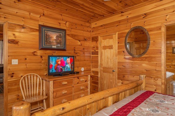 Dresser, TV, and chair in a bedroom at Hickernut Lodge, a 5-bedroom cabin rental located in Pigeon Forge