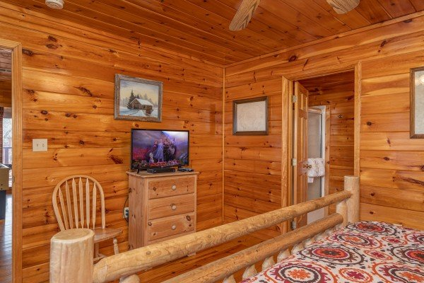Dresser, TV, and chair at Hickernut Lodge, a 5-bedroom cabin rental located in Pigeon Forge
