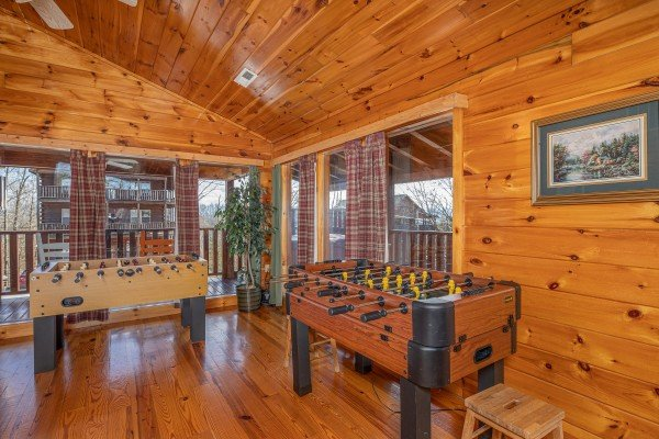 Two foosball tables in the loft at Hickernut Lodge, a 5-bedroom cabin rental located in Pigeon Forge